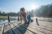 Jogging woman relaxing on lake pier at sunrise enjoying freshness from nature