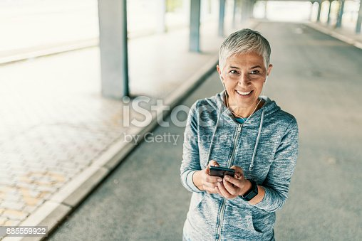 istock jogging woman setting music and running route on smart phone 885559922