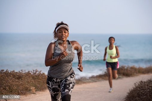 istock Jogging women running. Beginner plump woman and female pro runner during an outdoor workout on the coast line. 825122300