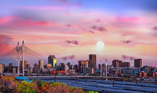 Long exposure shot of Johannesburg city skyline and Nelson Mandela bridge at sunset