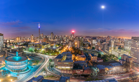 Johannesburg cityscape and moonlight, taken at sunset, showing the illuminated Council Chamber which is set to be the centre for the revitalisation and urban renewal of the precinct. Hillbrow residential area and the prominent communications tower and Ponte flats.