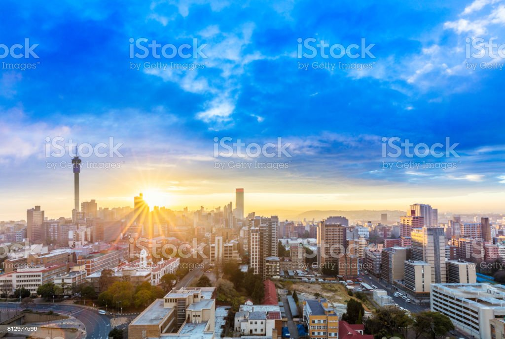 Johannesburg sunrise sunflare cityscape stock photo