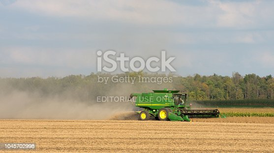 A John Deer combine harvesting a field of soy beans on a clear fall day in Southwestern Ontario, Canada.