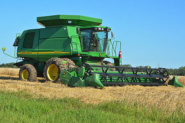 John Deere Combine Le Sueur, Minnesota, USA - August 1, 2015: Waiting for the day's temps to rise and the moisture content in the wheat to evaporate evaporation stock pictures, royalty-free photos & images