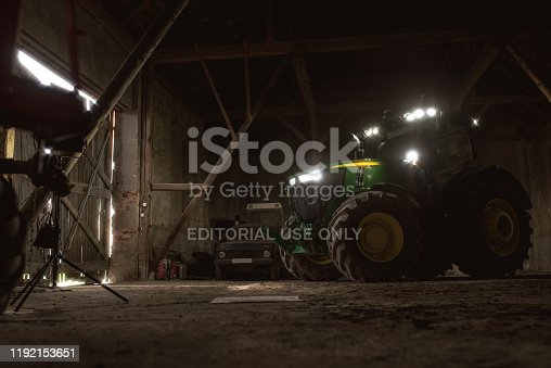John Deere modern  tractor parked in barn ready to drive outside for the field. 06 april 2017 Wroclaw, Poland.