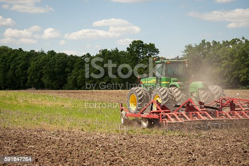Grabill, Indiana - June 13th, 2011: John Deere green tractor tilling the ground to prepare for summer planting of hay, corn, and soybeans in Indiana, USA. Driving through the field with a disk tiller.
