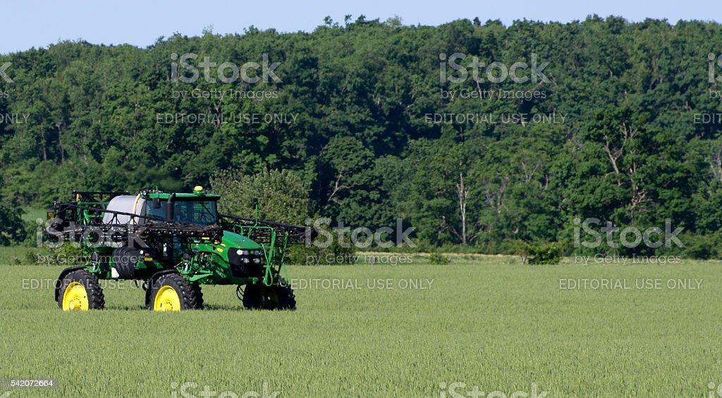 John Deere Sprayer in Field of Wheat stock photo