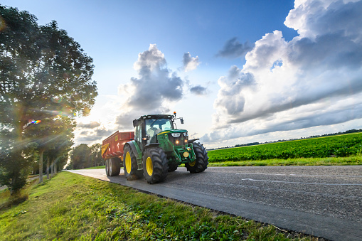 John Deere tractor hauling a loader on a country road in between agricultural fields. Potato field under a sky with impressive clouds after a summer thunderstorm in The Noordoostpolder, Flevoland, The Netherlands.