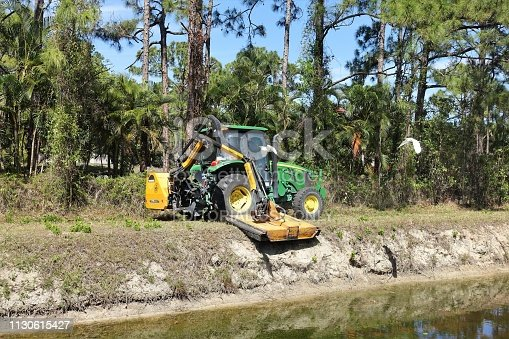 A John Deere tractor with a large mowing attachment cuts grass and brush on a south Florida canal bank in Palm Beach county.