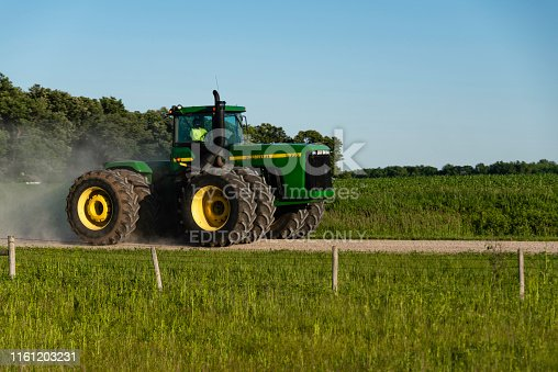 A person driving a John Deere agricultural tractor parallel to Interstate 90 near the city of Austin, Minnesota.