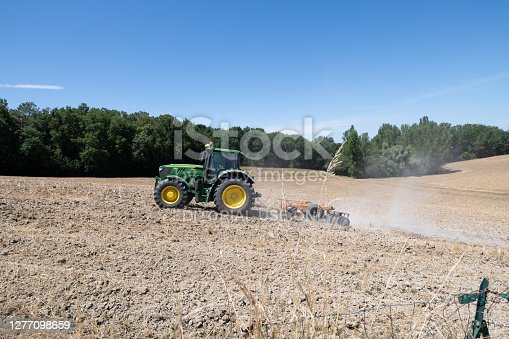 Bergerac, France: July 2020; John Deere tractor ploughing a field with a disc harrow in summer