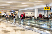 New York City, New York, USA - April 27, 2018:  View inside John F. Kennedy International Airport at the Delta Airlines gate on a typical morning with passengers in view.