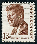 Frontal view of the obverse (heads) side of a silver half Dollar minted in 1964. Depicted is a profile portrait of John F. Kennedy and comes to honor his memory.