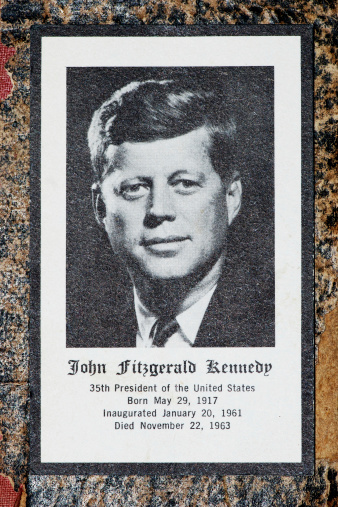 Borgosesia, Italy - September 4, 2011: John Fitzgerald Kennedy funeral prayer obituary card, studio shot of the card on an old book cover. Printed by Jefferies & Manz Inc. Phila., Pa.