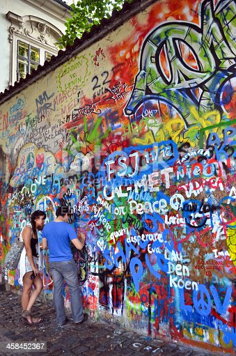 Prague, Czech Republic- July 8, 2012: Two local people painting their names on John Lennon Wall monument at the city of Prague.