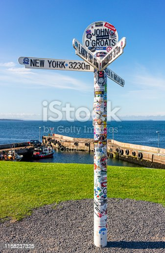 John O'Groats, Scotland - A sign marking John O'Groats, famous as the destination for the journey across the UK from Lands End. The sign is covered in stickers.