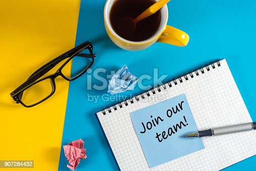 477419728istockphoto Join our team - message at blue note near morning coffee cup at blue and yellow background. Hiring and new job concept 907284432