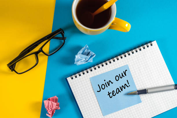 Join our team - message at blue note near morning coffee cup at blue and yellow background. Hiring and new job concept stock photo