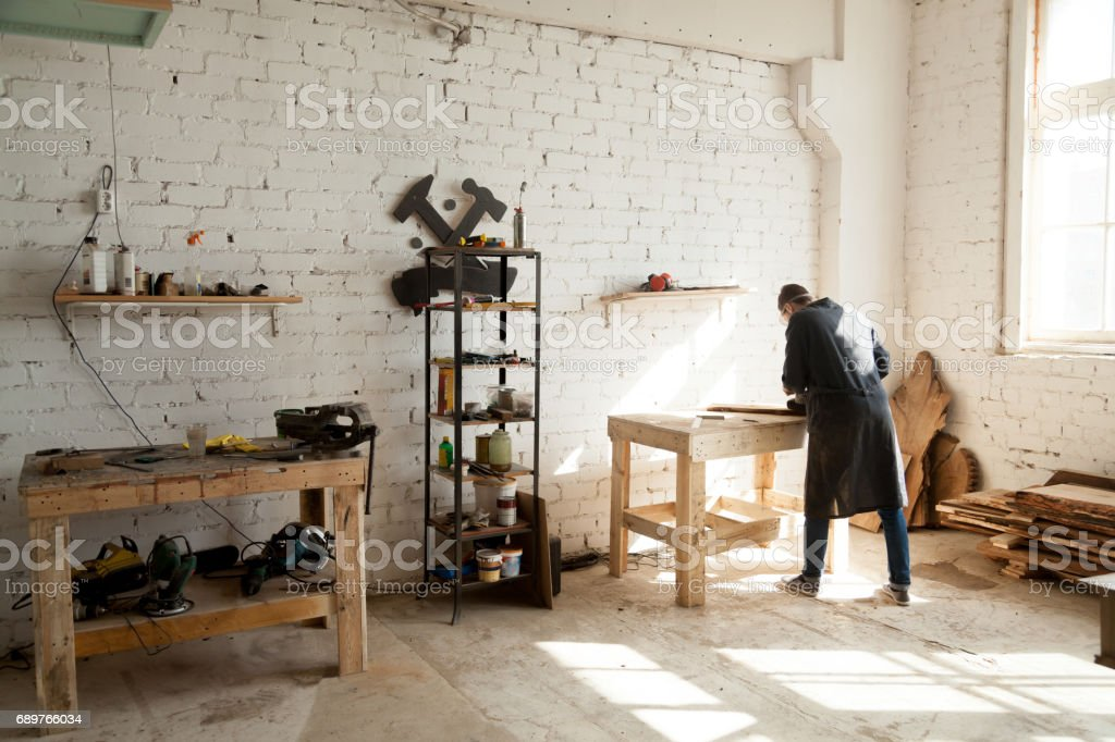 Joiner working at workbench in small carpentry stock photo
