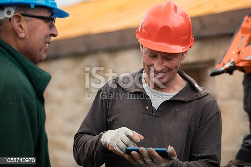 Two mid-adult male joiners standing outside looking at a mobile phone while taking a break.