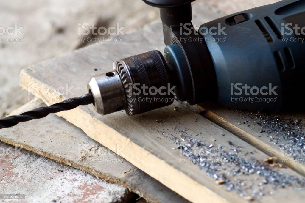 Joinery tools in a workshop. Drill on a wooden workshop table. Dark background royalty-free stock photo
