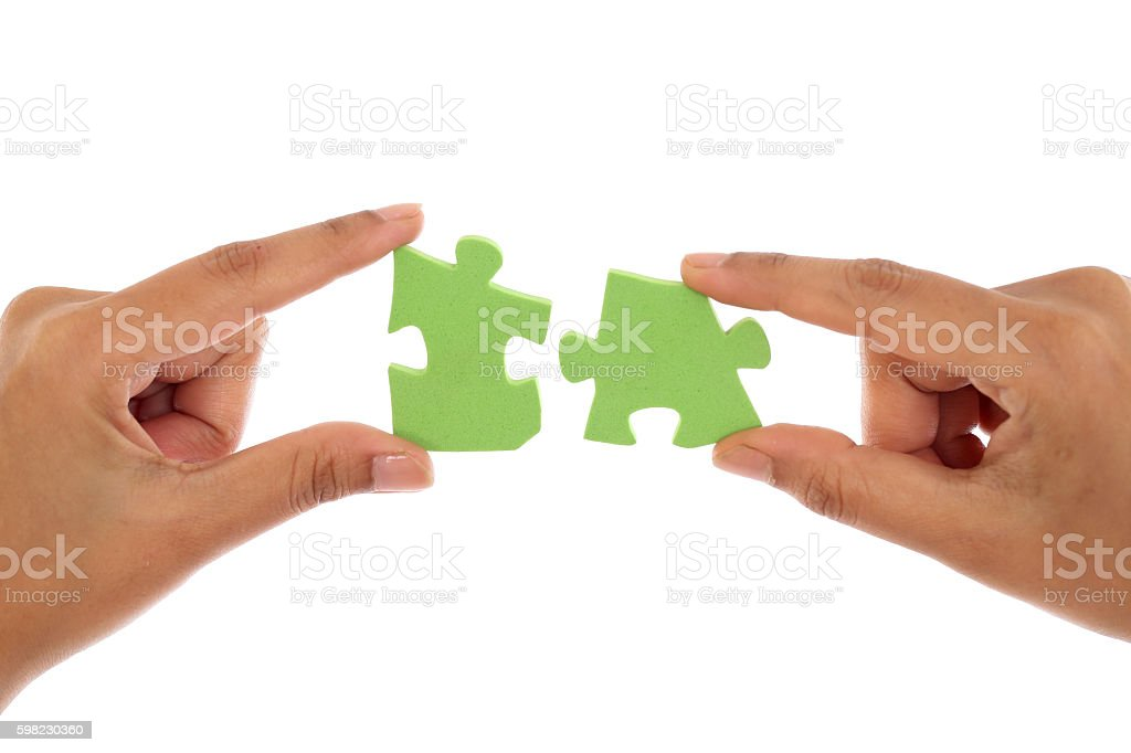 Joining Jigsaw puzzle pieces against white background foto royalty-free