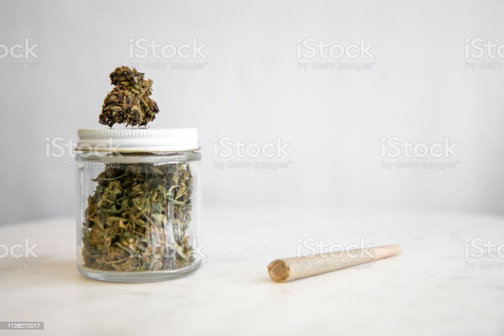 Joint and Cannabis Glass Jar on White Marble - Cannabis Dispensary Products stock photo