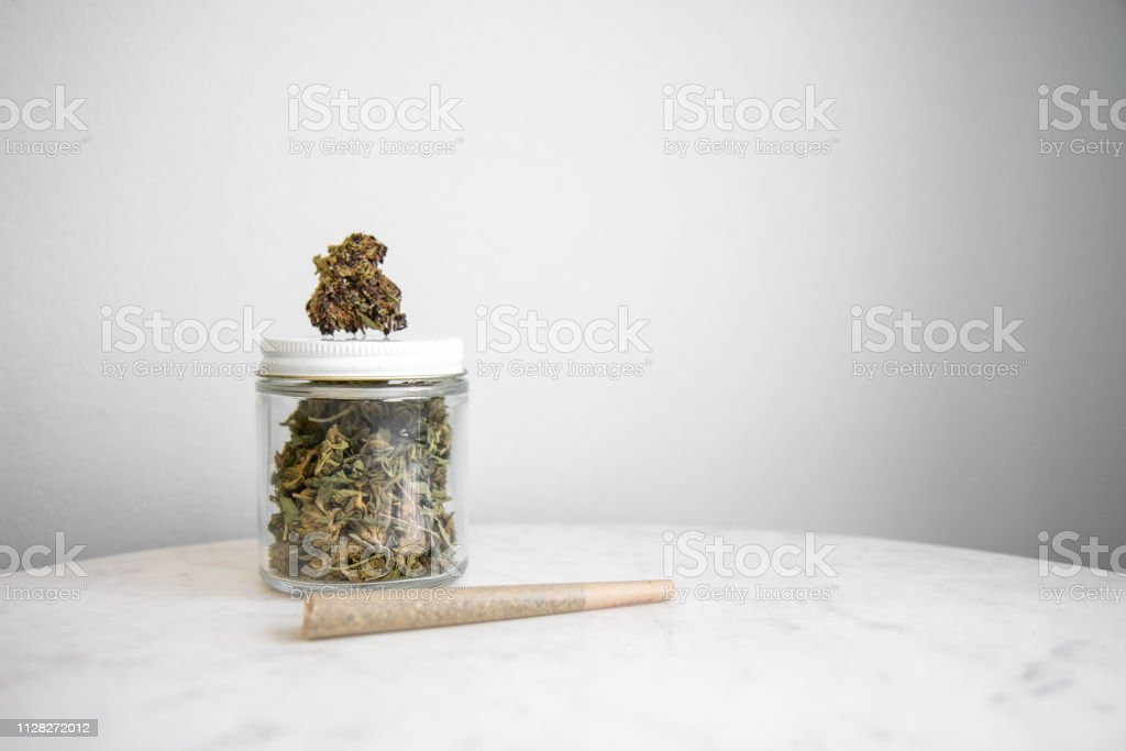 Joint, Bud and Cannabis Glass Jar on White Marble - Cannabis Dispensary Products stock photo