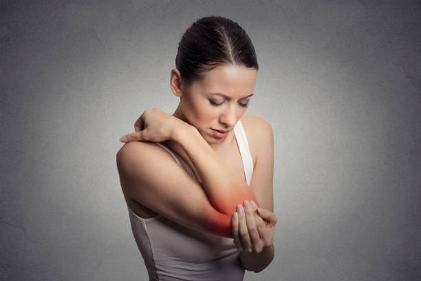 Joint inflammation indicated with red spot on female's elbow. Arm pain and injury concept. Joint inflammation indicated with red spot on female's elbow. Arm pain and injury concept. Closeup portrait woman with painful elbow on gray background gout stock pictures, royalty-free photos & images