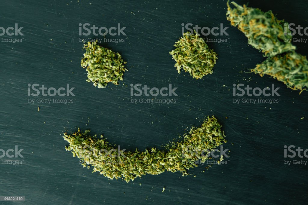 Joint weed Macro of cannabis buds marijuana with trichomes and crushed weed on a black table close up Smile of cannabis crushed weed royalty-free stock photo