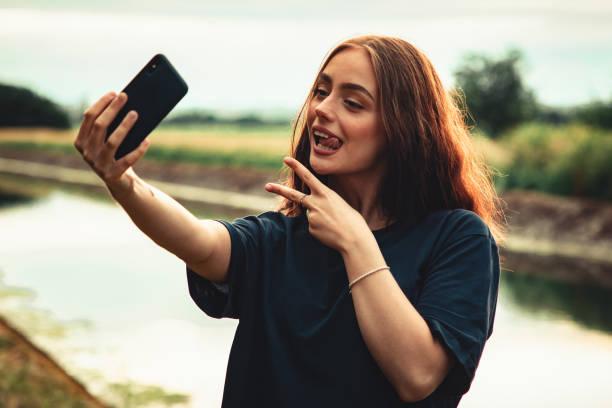 Joking Around Teenage Woman Vlogging with Mobile Phone stock photo