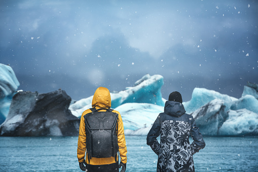 Man and woman watching Jökulsárlón glacial lagoon on a snowy day (south Iceland).
