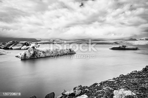 Jokulsarlon glacier lagoon in Iceland. Long exposure shot makes the water and the sky silky. Long exposure, glacier, moody concepts, black and white, vintage.