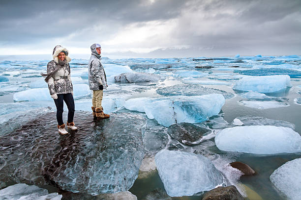Jokulsarlon tourists Extremely beautiful tourists stand on the massive icebergs in lake Jokulsarlon in Iceland in winter glacier lagoon stock pictures, royalty-free photos & images