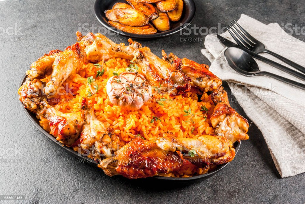 Jollof rice with chicken and plantains stock photo