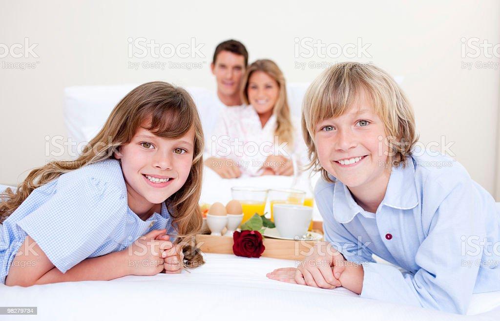 Jolly famiglia avendo colazione seduta sul letto foto stock royalty-free