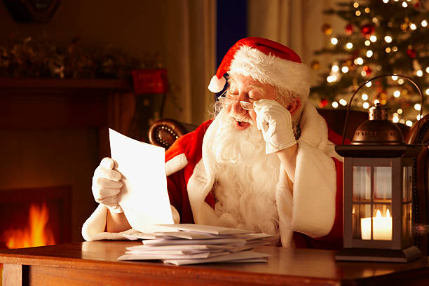 Jolly Father Christmas Reading letters from children stock photo