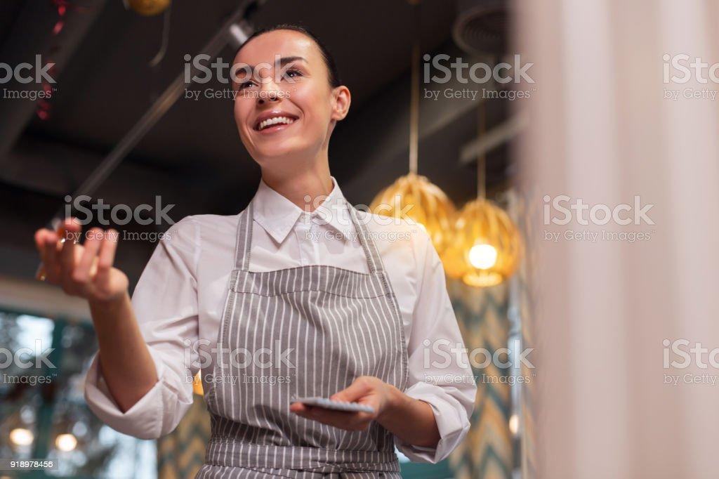New menu. Optimistic energetic nice waitress moving hand while...