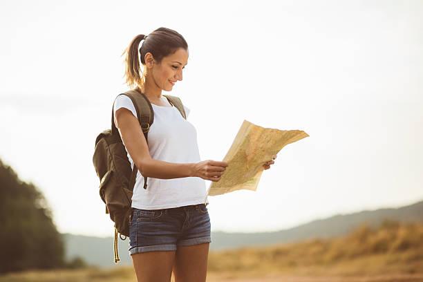 jolly hiker girl holding map - geführtes lesen stock-fotos und bilder