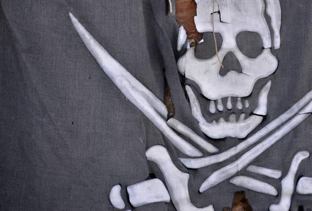 Jolly Roger o bandera pirata con calavera y láminas cruzadas de la textura de la tela, cierre - hasta - foto de stock