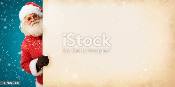 istock Jolly Santa Claus peeking out of an old paper banner 607653666