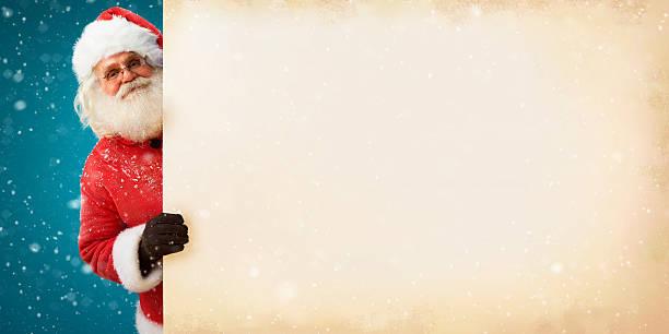 jolly santa claus peeking out of an old paper banner - holiday background zdjęcia i obrazy z banku zdjęć
