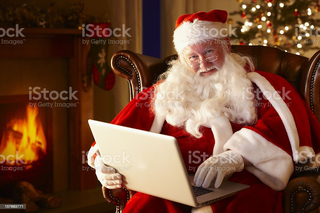 Jolly Santa working on a laptop computer royalty-free stock photo