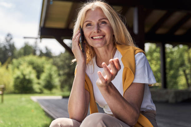 Jolly woman talking on smartphone outside holiday home stock photo