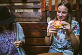 Happy Female Friends Having Dinner And Beer And Laughing Broadly on Night Out at Restaurant
