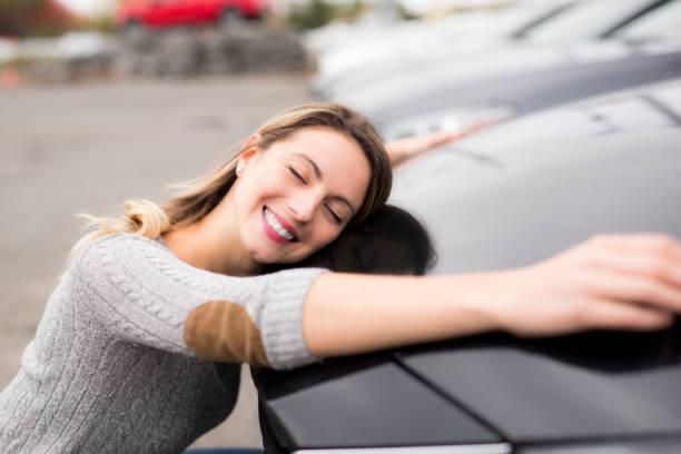 lustiger junge fahrerin umarmt ihr neues auto - teller kaufen stock-fotos und bilder