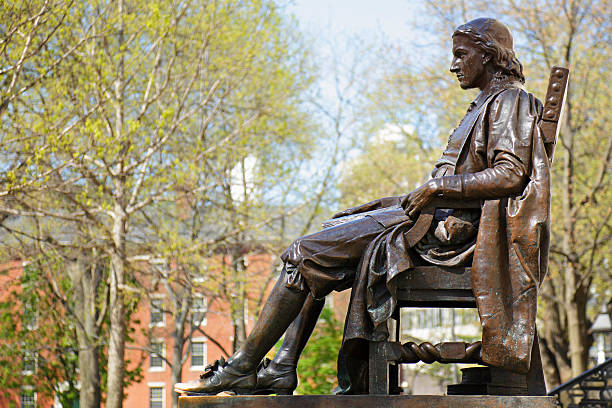 """Jon Harvard monument with trees and campus in background """"John Harvard monument (c. 1884) by Daniel Chester French (Cambridge, Massachusetts)."""" harvard university stock pictures, royalty-free photos & images"""