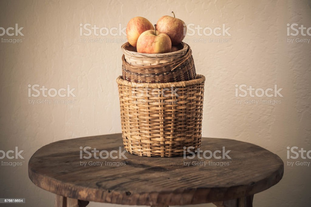 Jonagold apples in a basket on wooden table against white wall background, Autumn harvest background, Happy thanksgiving stock photo