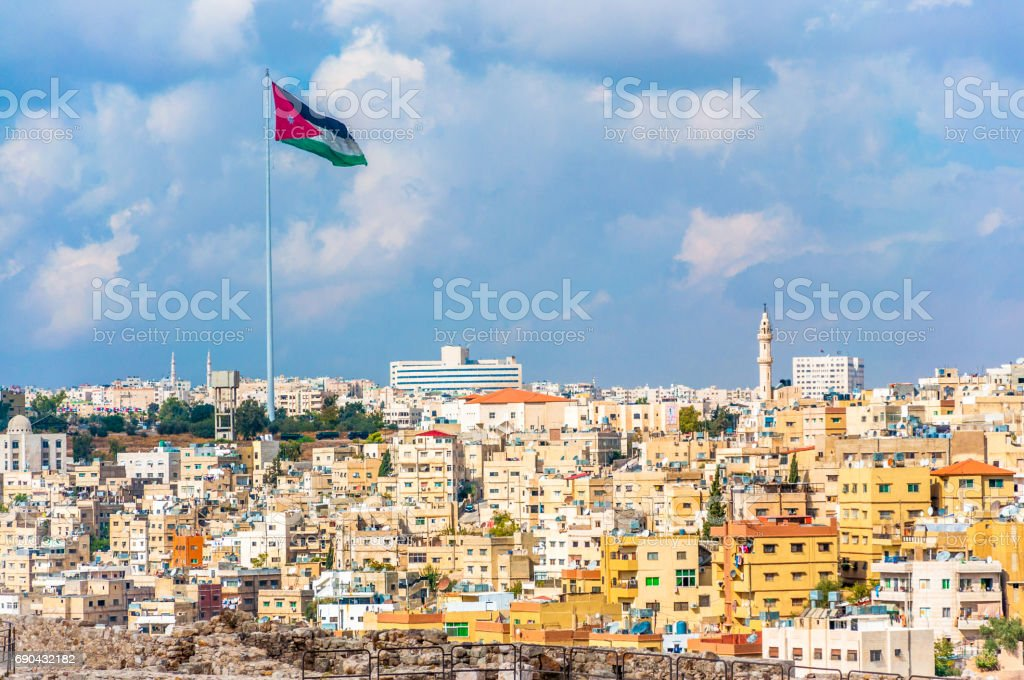 Jordan flag in Amman, cloudy sky background stock photo