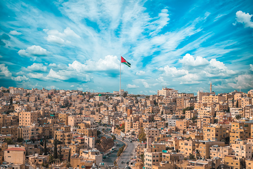 Jordan flag in Amman, landscape view of cloudy sky background